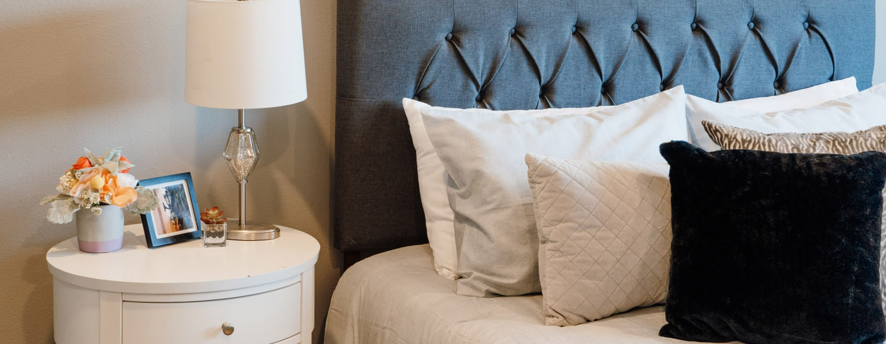 bedside table with lamp next to neatly made bed